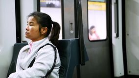 Рубашка азиатской женщины нося белая sportive сидит в двигая поезде и смотрит вокруг видеоматериал