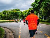 Рубашка азиатской носки бегуна оранжевая Jogging в городе Central Park стоковые изображения rf