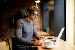 Рубашка бизнесмена взгляда со стороны нося сидя на таблице в кафе и компьтер-книжке польз стоковое изображение