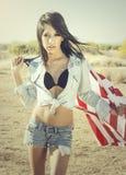 Рубашка джинсовой ткани женщины нося держа американский флаг Стоковые Фото