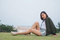 Рубашка зеленого цвета женщины сидя на траве стоковое изображение rf