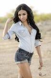 Рубашка и шорты джинсовой ткани женщины нося стоковое фото rf
