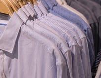 Рубашка людей на вешалке Официальная носка людей в магазине Строка вешалки торгового центра Белая striped равномерная рубашка Стоковое Фото