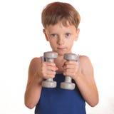 Рубашка мальчика голубая делая тренировки с гантелями над белым backgro Стоковая Фотография RF