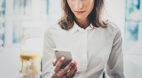 Рубашка молодой бизнес-леди портрета нося белая используя современные руки smartphone Сообщение sms чтения девушки в работе Стоковое фото RF