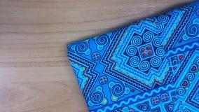 Рубашка синих хлопков детализирует текстуру на деревянной предпосылке таблицы Стоковые Изображения RF