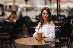 Рубашка стильной счастливой молодой женщины нося белая Она держит кофе солнечные очки портрета девушки ся стоковое фото rf