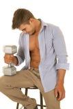 Рубашка человека голубая открытая сидит с весом в кулаке Стоковая Фотография