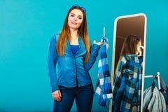 Рубашка шотландки модной женщины пробуя перед зеркалом Стоковое Фото