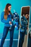 Рубашка шотландки модной женщины пробуя перед зеркалом Стоковое Изображение RF