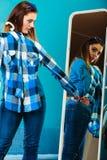 Рубашка шотландки модной женщины пробуя перед зеркалом Стоковое фото RF