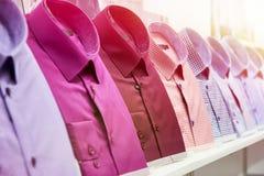 Рубашки людей в магазине одежды стоковое изображение