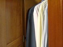 Рубашки платья в шкафе - шкаф двери стоковое фото