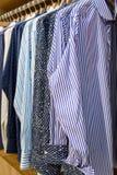 Рубашки покрашенных людей вися в магазине Стоковые Изображения RF