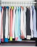 рубашки рубашки человека на вешалках Стоковые Изображения