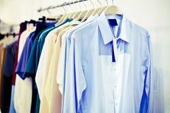 Рубашки человека с биркой на вешалках стоковые фото
