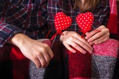Рубашки шотландки пар любовной истории Romance держа красный цвет вручают 2 сердцам молодой любящий день валентинки женщины челов Стоковое фото RF