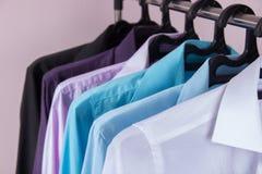 Рубашки ` s покрашенных людей которые висят на вешалках Стоковые Изображения RF