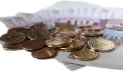 Рубли монеток против предпосылки 500 рублей банкнот isolared на белом конце предпосылки вверх Стоковые Фотографии RF