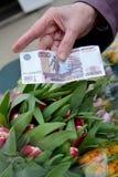 500 рублей в руке пожилой женщины на фоне тюльпанов Стоковая Фотография