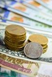 Рубли монетки над примечаниями доллара Стоковые Фото