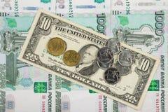 Рубль монеток и евро на счете 10 долларов который лежит на куче тысяч-русских банкнот Стоковая Фотография RF