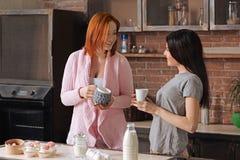 2 дружелюбных девушки держа чашки Стоковая Фотография