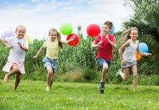 4 дружелюбных дет бежать на зеленой лужайке Стоковая Фотография