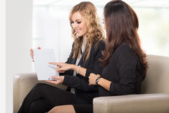 2 дружелюбных коммерсантки сидя и обсуждая новое usin идей Стоковое Фото
