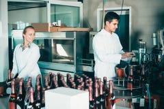 2 дружелюбных коллеги держа бутылки вина Стоковая Фотография