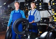 2 дружелюбных коллеги мужчин работая с автошинами мотоцикла Стоковое фото RF
