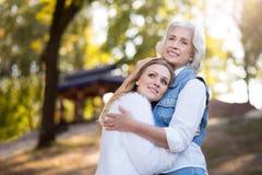 2 дружелюбных красивых женщины обнимая один другого в парке Стоковые Изображения RF