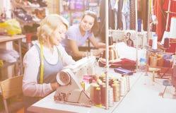 2 дружелюбных портноя женщин работая с швейными машинами Стоковая Фотография