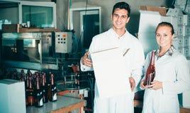 2 дружелюбных работника стоя в упаковывая разделе на человеке вина Стоковые Фото