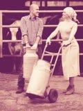2 дружелюбных фермера держа вагонетку с молоком Стоковое Фото