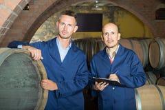 2 дружелюбных люд в формах принимая примечания в погребе с вином wo Стоковые Фото