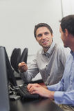 2 дружелюбных люд говоря сидеть перед компьютером Стоковое Фото