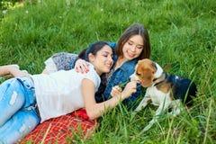 2 друзья и бигля Молодая счастливая женщина 2, имеющ потеху Стоковая Фотография RF
