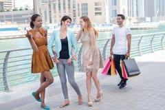друзья идут ходить по магазинам Красивые девушки в платьях обнимают whil парня Стоковое Изображение RF