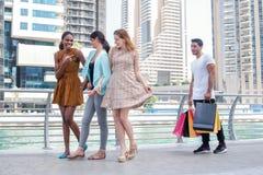 друзья идут ходить по магазинам Красивые девушки в платьях обнимают whil парня Стоковые Изображения RF