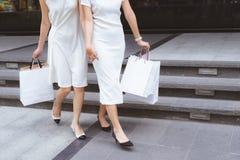 друзья идут ходить по магазинам Прогулка 2 молодых женщин на торговом центре с Стоковое Изображение RF