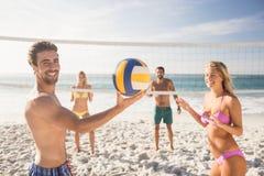 друзья пляжа играя волейбол Стоковое фото RF