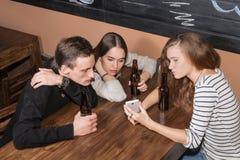 друзья смотря smartphone Стоковая Фотография RF