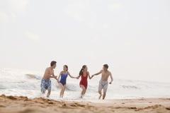 4 друз бежать из воды на песчаном пляже Стоковое Изображение