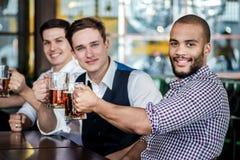 4 друз бизнесменов выпивают пиво и тратят время совместно в a Стоковая Фотография RF