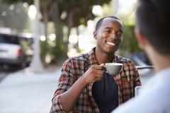 2 друз взрослых мужчины сидят говорить над кофе вне кафа Стоковые Изображения RF