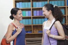 2 друз встречая на студии йоги, держа кладут в мешки Стоковые Изображения