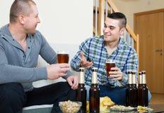 2 друз выпивая пиво дома Стоковое Изображение