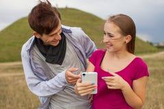 2 друз в парке с мобильным телефоном взрослые молодые Стоковая Фотография RF