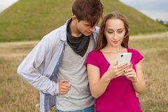 2 друз в парке с мобильным телефоном взрослые молодые Стоковое фото RF